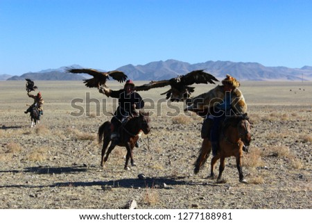 """BAYAN-OLGII PROVINCE, MONGOLIA - OCTOBER 07, 2018: Mongolians horsemen in traditional clothing with golden eagles posing during the festival of name """"The Golden Eagle Festival"""" #1277188981"""