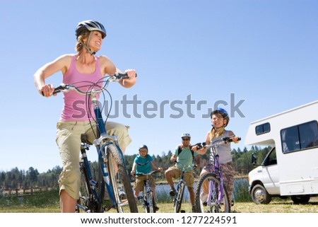 Family riding bikes in countryside on motor home vacation #1277224591