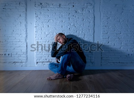 Young devastated depressed man crying sad feeling hurt suffering Depression in Sadness Emotional pain and human expression Loneliness and Heartbroken concept with copy space and dark mood light. #1277234116