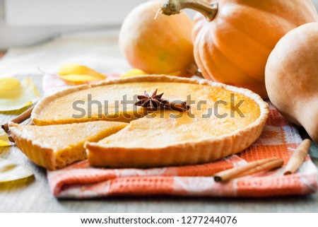 Homemade spicy pumpkin pie with cinnamon on a table with pumpkings at background #1277244076
