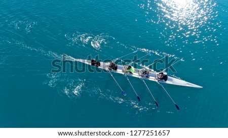Aerial drone bird's eye view of sport canoe operated by team of young men in emerald clear sea Royalty-Free Stock Photo #1277251657
