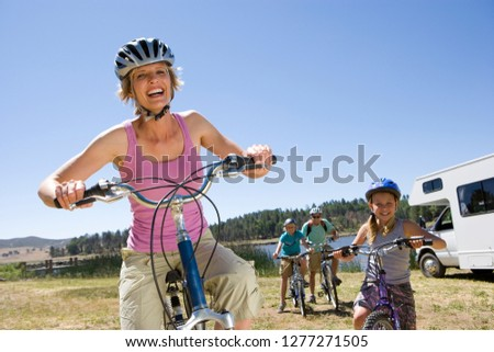 Family riding bikes in countryside on motor home vacation #1277271505
