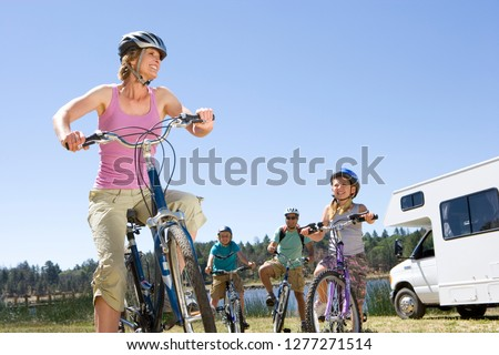 Family riding bikes in countryside on motor home vacation #1277271514