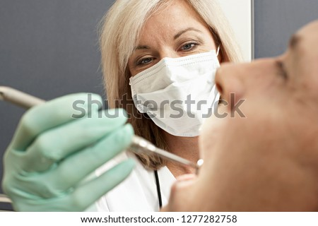 Female dentist in surgical mask giving patient dental check up using mirror #1277282758