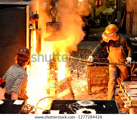 workers in a foundry casting a metal workpiece - safety at work and teamwork  #1277284426