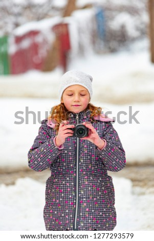 A girl walks in winter with a camera and takes pictures of sights in a snow-covered city. #1277293579