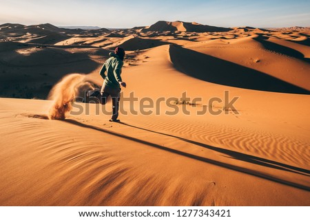 A girl runs down a sand dune in Morocco lifting a spray of sand behind her #1277343421