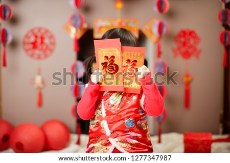 Chinese baby girl  traditional dressing up with a FU means lucky red envelope against  FU means lucky ornament background #1277347987