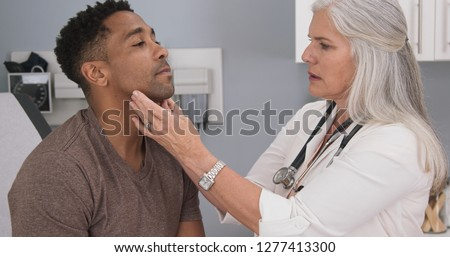 Close up of senior female doctor examining male patients neck Royalty-Free Stock Photo #1277413300