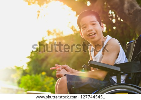 Disabled child on wheelchair is playing, learning and exercise in the outdoor city park like other people,Lifestyle of special child,Life in the education age of children,Happy disability kid concept. #1277445451