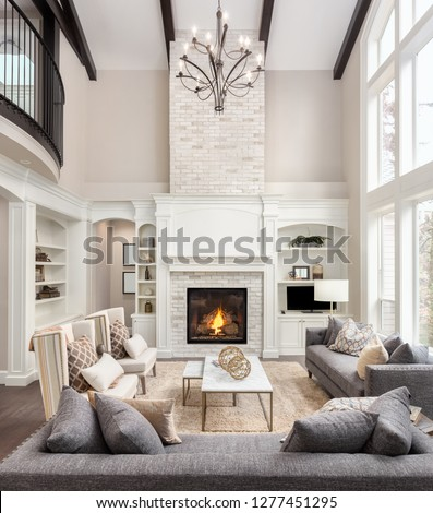 Beautiful living room interior with hardwood floors and fireplace in new luxury home. Large bank of windows hints at exterior view #1277451295