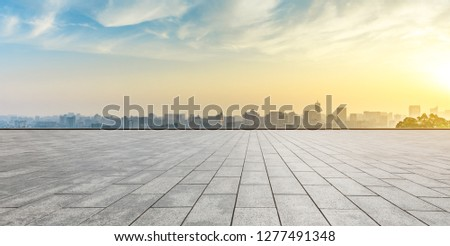 Panoramic city skyline and buildings with empty square floor at sunrise Royalty-Free Stock Photo #1277491348