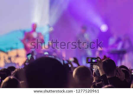 Use advanced mobile recording, fun concerts and beautiful lighting, Candid image of crowd at rock concert, Close up of recording video with smartphone, Enjoy the use of mobile photography #1277520961