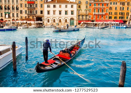 Gondolier carries tourists on gondola Grand Canal of Venice, Italy. #1277529523