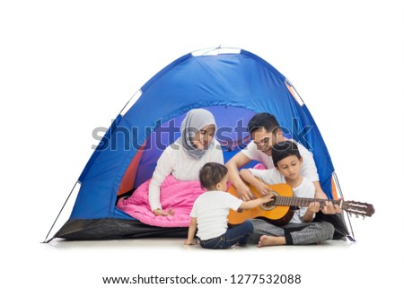 Picture of a happy family playing guitars in the tent while camping in the studio, isolated on white background