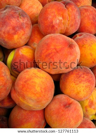 Many bright tasty peaches laying in the market