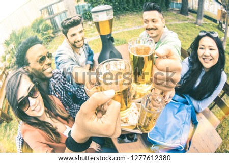 Multiracial group of happy friends millennials eating and toasting beer at garden barbecue party - Multiethnic hangout concept with young people enjoying picnic time together - Warm vintage filter
