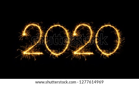 Happy New Year 2020 text handmade written sparkles fireworks. Beautiful Shiny Golden numbers isolated on black background for design #1277614969