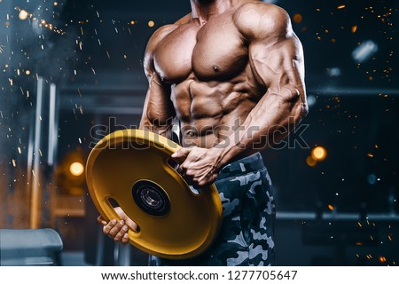 Brutal strong bodybuilder athletic man pumping up muscles workout bodybuilding concept background - muscular bodybuilder handsome men doing exercises in gym naked torso sport nutrition concept #1277705647