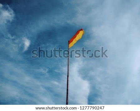 red yellow warning beach flag #1277790247