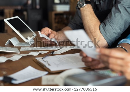 Mature smalll business owners calculating finance bills of their activity. Business people using calculator to work. Closeup hands of man and woman calculating bills and expenses.  #1277806516