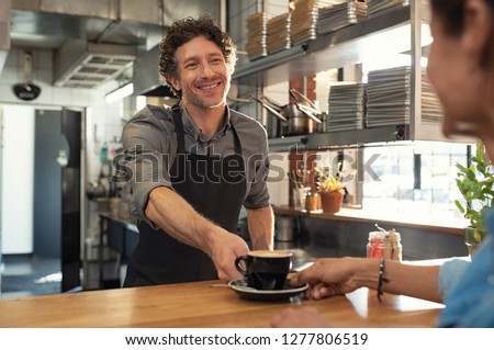 Smiling mature waiter giving hot coffee to woman at cafeteria. Happy man standing behind counter giving a cappuccino to woman in a coffee shop. Portrait of cheerful man serving customer at restaurant. Royalty-Free Stock Photo #1277806519