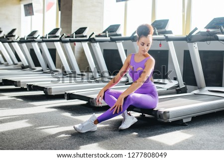 Sport world. Young fitness girl in sport wear relaxing on the treadmill in the gym, Exercise working out with copy space. Runnig machine #1277808049