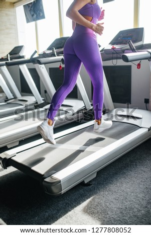 Sport world. Legs woman in violet sportswear running on a treadmill in front of window at gym. Jogging her way to good health. #1277808052