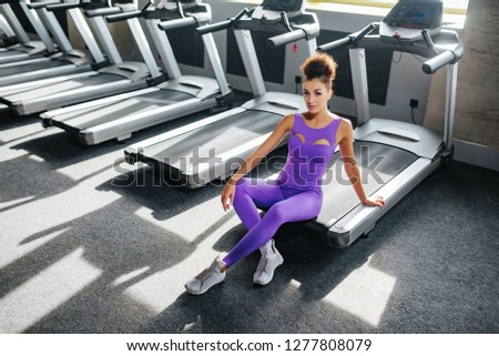 Woman in violet sportswear relaxing after running on a treadmill in front of window at gym. Jogging her way to good health. #1277808079