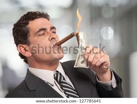 Rich businessman lighting cigar with $100 dollar bill Royalty-Free Stock Photo #127785641