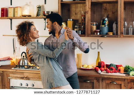 Happy moments. Young african-american couple in love dancing in kitchen, copy space Royalty-Free Stock Photo #1277871127