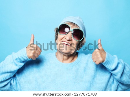 Lifestyle, emotion and people concept: Funny old lady wearing blue sweater, hat and sunglasses showing victory sign. #1277871709