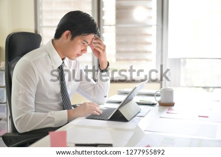 Businessman analyzing financial statistics displayed on the tablet screen. #1277955892