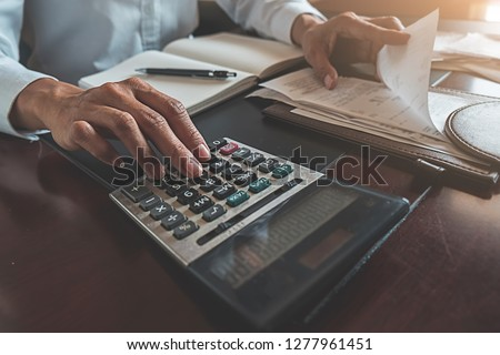 Woman with bills and calculator. Woman using calculator to calculate bills at the table in office. Calculation of costs. #1277961451