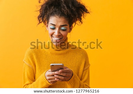 Excited african woman wearing sweater standing isolated over yellow background, holding mobile phone #1277965216