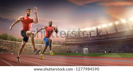 Male athletes sprinting. Two men in sport clothes run at the running track in professional stadium #1277984590