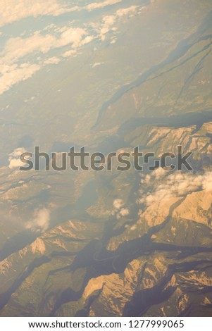 Clouds over snow clad Austrian Alps mountains seen from an airplane window, Europe #1277999065