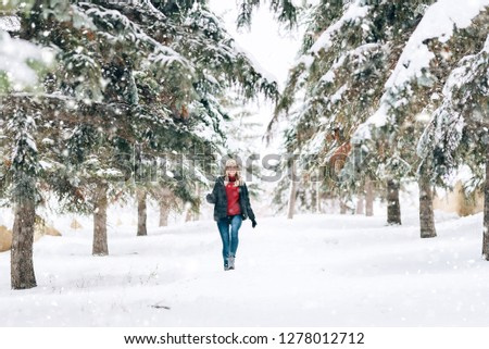 girl in a fashionable winter hat with a leopard print rejoices in the snow #1278012712