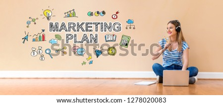 Marketing plan with young woman with headphones using a laptop computer and a pencil #1278020083