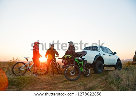 Friends Cyclists Resting near the Pickup Off Road Truck after Enduro Bike Riding in the Mountains at Warm Autumn Sunset. MTB Adventure and Car Travel Concept. #1278022858