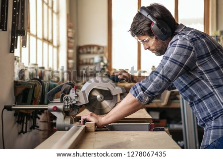 Skilled woodworker wearing safety gear using a mitre saw to cut a piece of wood while working alone in his woodworking studio #1278067435