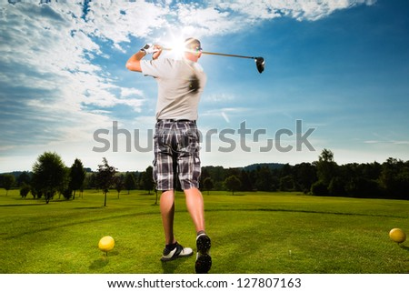 Young golf player on course doing golf swing, he presumably does exercise #127807163