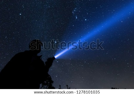 Blur shadow of man with flashlight point to the starry sky at midnight. Royalty-Free Stock Photo #1278101035