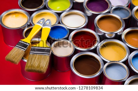 Full Buckets of rainbow colored oil paint on red background #1278109834