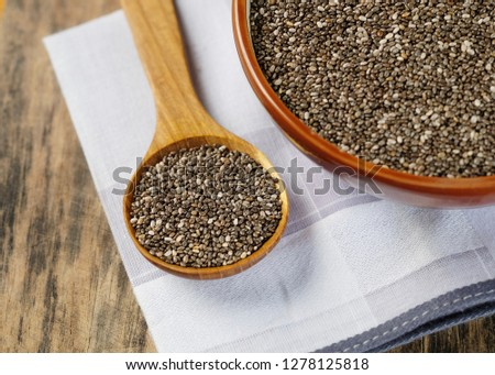 Nutritious Chia seeds in a wooden spoon on wooden table. #1278125818