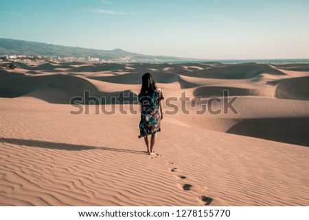 woman in dress walking at the beach of Maspalomas Gran canaria with huge sand dunes desert, golden sand dunes Maspalomas with girl in dress #1278155770