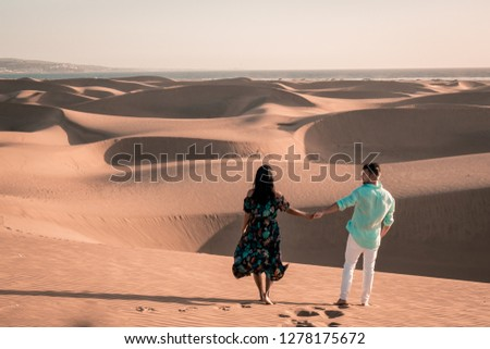 couple walking at the beach of Maspalomas Gran Canaria Spain, men and woman at the sand dunes desert of Maspalomas #1278175672