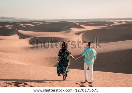 couple walking at the beach of Maspalomas Gran Canaria Spain, men and woman at the sand dunes desert of Maspalomas #1278175675