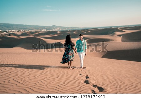 couple walking at the beach of Maspalomas Gran Canaria Spain, men and woman at the sand dunes desert of Maspalomas #1278175690