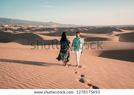 couple walking at the beach of Maspalomas Gran Canaria Spain, men and woman at the sand dunes desert of Maspalomas #1278175693